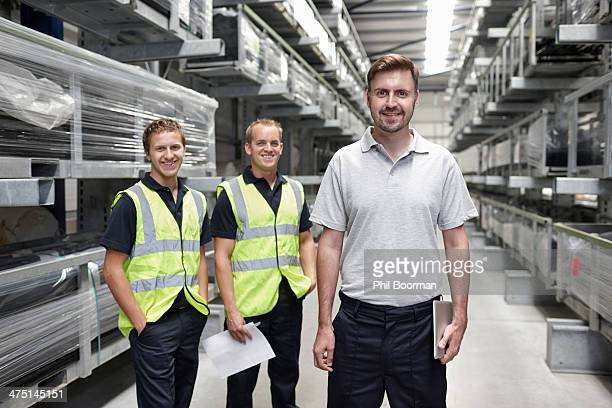 Portrait of three workers in engineering warehouse