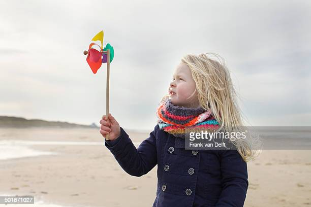Portrait of three year old girl with paper windmill on beach, Bloemendaal aan Zee, Netherlands