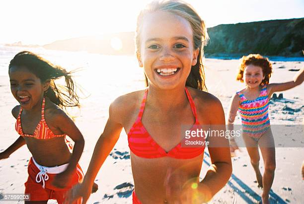 portrait of three young girls running on the beach