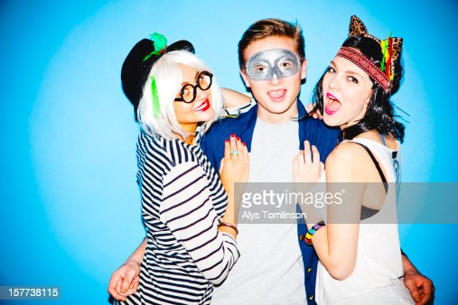 Portrait of three young people celebrating : Stock Photo