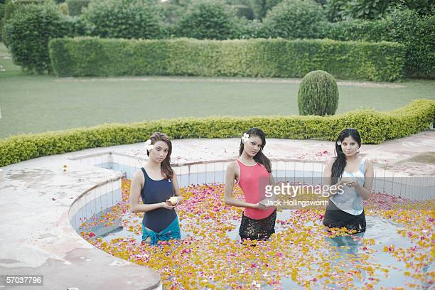 Portrait of three young women holding candles and standing in a swimming pool
