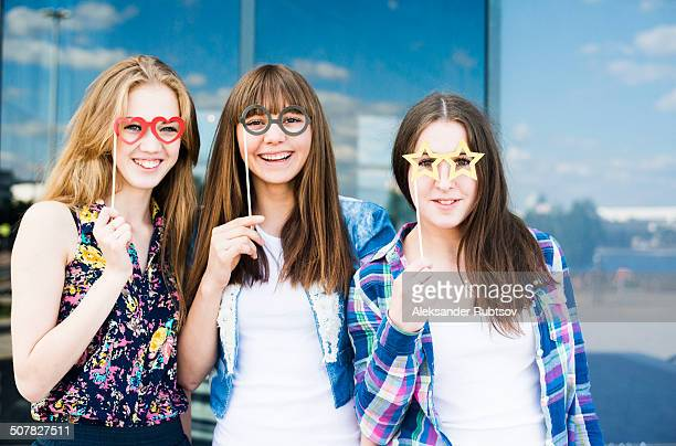 Portrait of three young women holding up spectacle costume masks