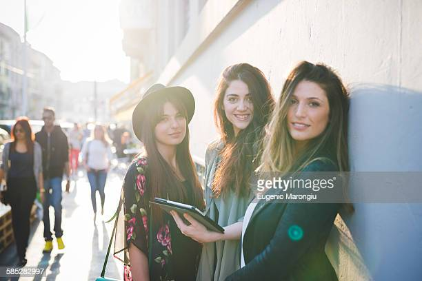 Portrait of three young women using digital tablet on city street