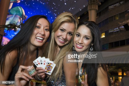 Portrait of three young women with playing cards, gambling chips and champagne in front of casino, L : Stock Photo