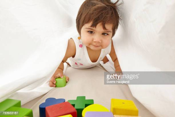 Portrait of toddler, crawling between sheets
