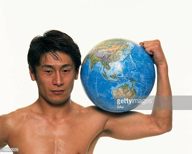 Portrait of topless mid adult man holding a globe over shoulder, Front View