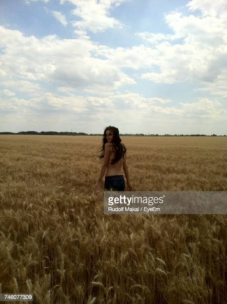 Portrait Of Topless Woman Standing Amidst Wheat Field