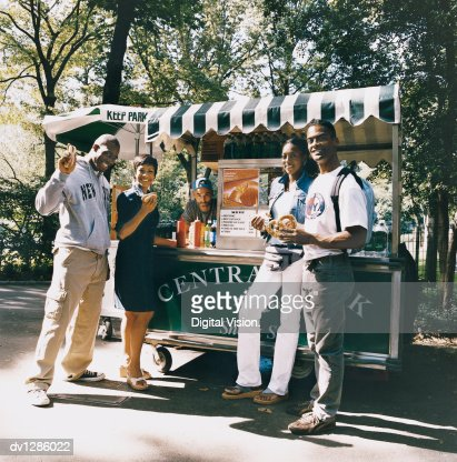 Portrait of Tourists in Central Park in New York City Holding Food in Front of a Hot Dog Stand : Stock Photo