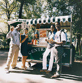 Portrait of Tourists in Central Park in New York City Holding Food in Front of a Hot Dog Stand