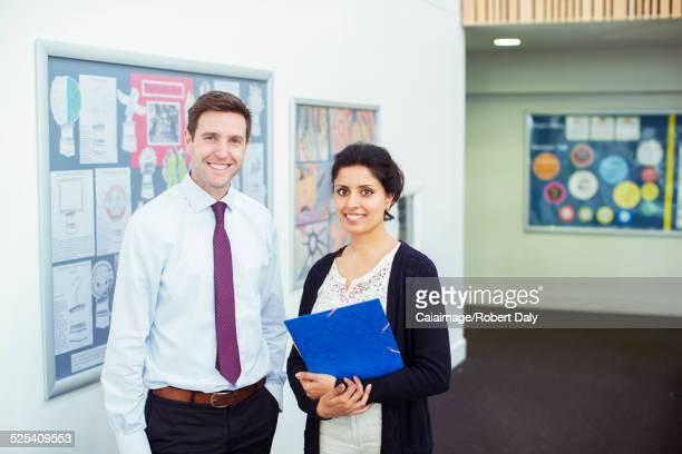 Portrait of tow smiling teachers standing in school corridor