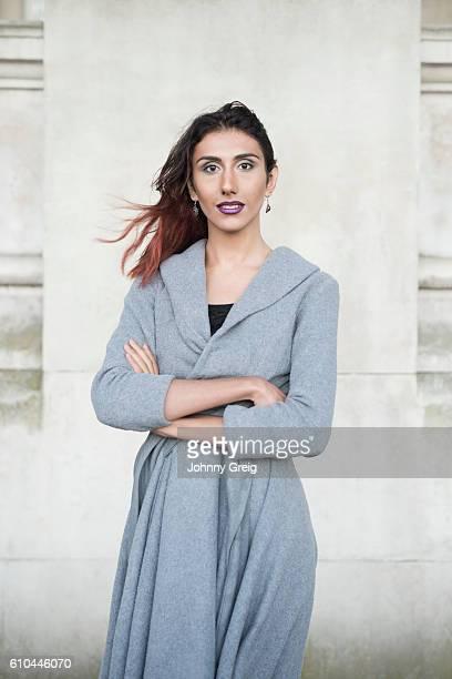 Portrait of transgender female in grey cardigan, arms folded