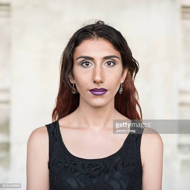 Portrait of transgender female wearing black top looking towards camera