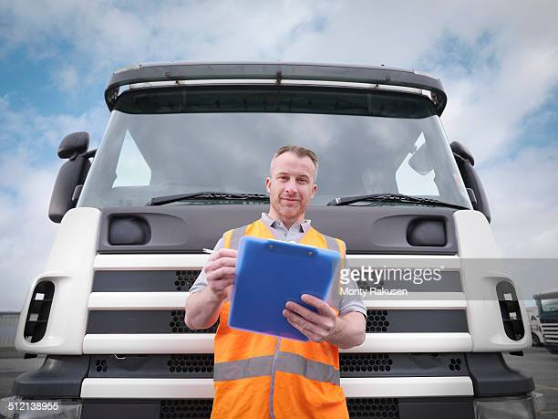 Portrait of truck driver checking notes on clipboard