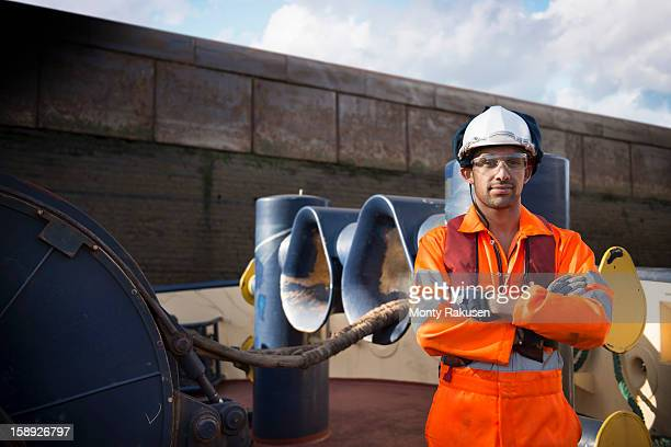 Portrait of tug worker wearing hard hat and protective goggles with arms folded