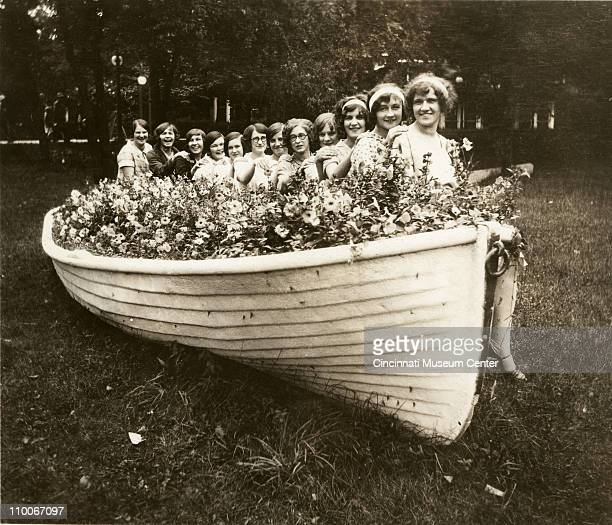 Portrait of twelve young women and girls as they pose seated on the gunwale of a flower filled boat parked on the grass Cedar Point Ohio 1925