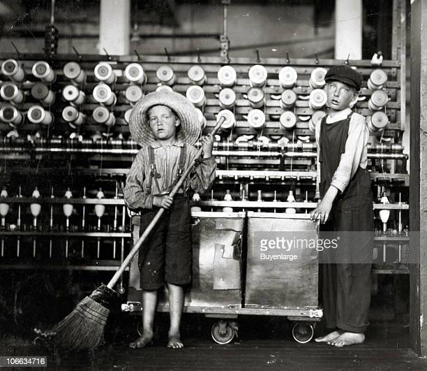 Portrait of twelveyearold doffer Ronald Webb and sevenyearold sweeper Frank Robinson as they pose in the spinner room of the Roanoke Cotton Mills...