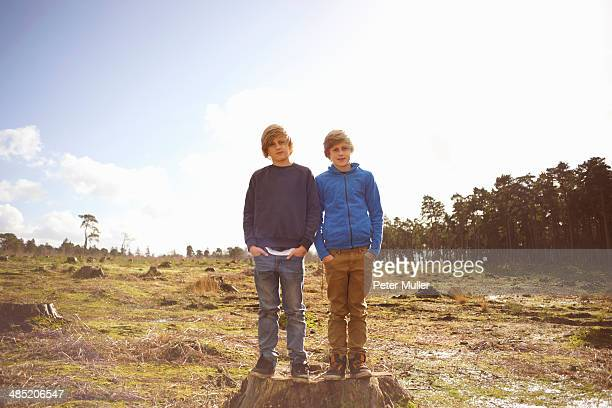 Portrait of twin brothers in forest clearing