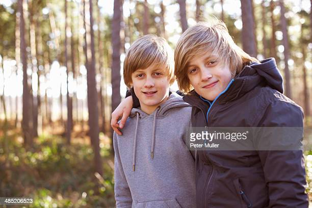 Portrait of twin brothers in forest