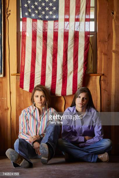 Portrait of twin Mixed Race teenage girls posing under American flag