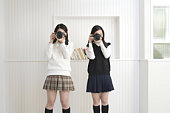 Portrait of twin sisters holding cameras and photographing, front view