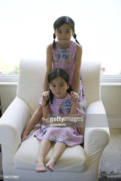 Portrait of twin sisters on an armchair
