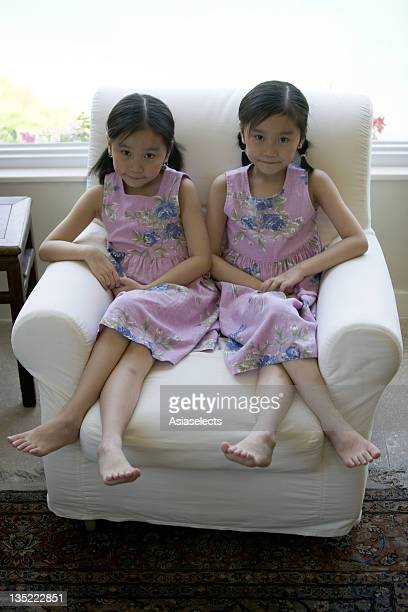 Portrait of twin sisters sitting on an armchair