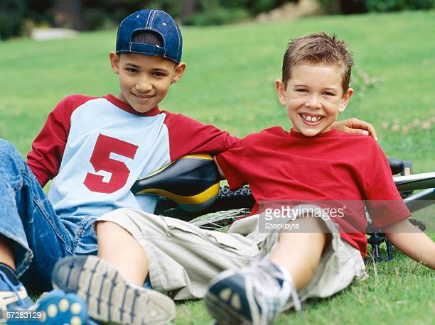 Portrait of two boys lying on the grass