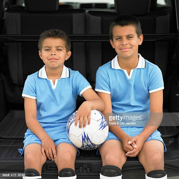 Portrait of two boys sitting at the back of a car wearing soccer uniform