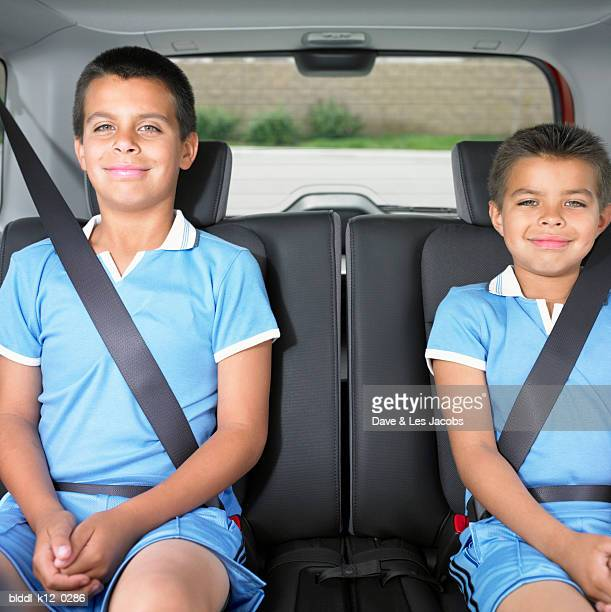Portrait of two boys sitting in the back seat of a car