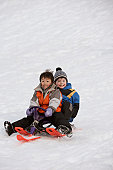 Portrait of two boys sliding down a hill on a toboggan