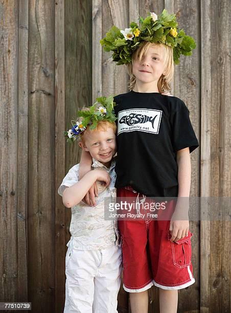Portrait of two boys wearing garlands of flowers.