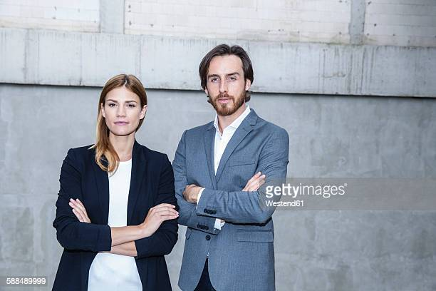 Portrait of two business people standing side by side with crossed arms