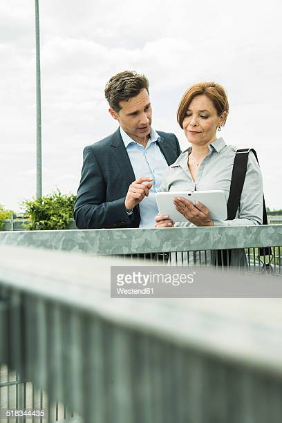 Portrait of two business people with tablet computer