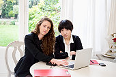 Portrait of two business woman using laptop