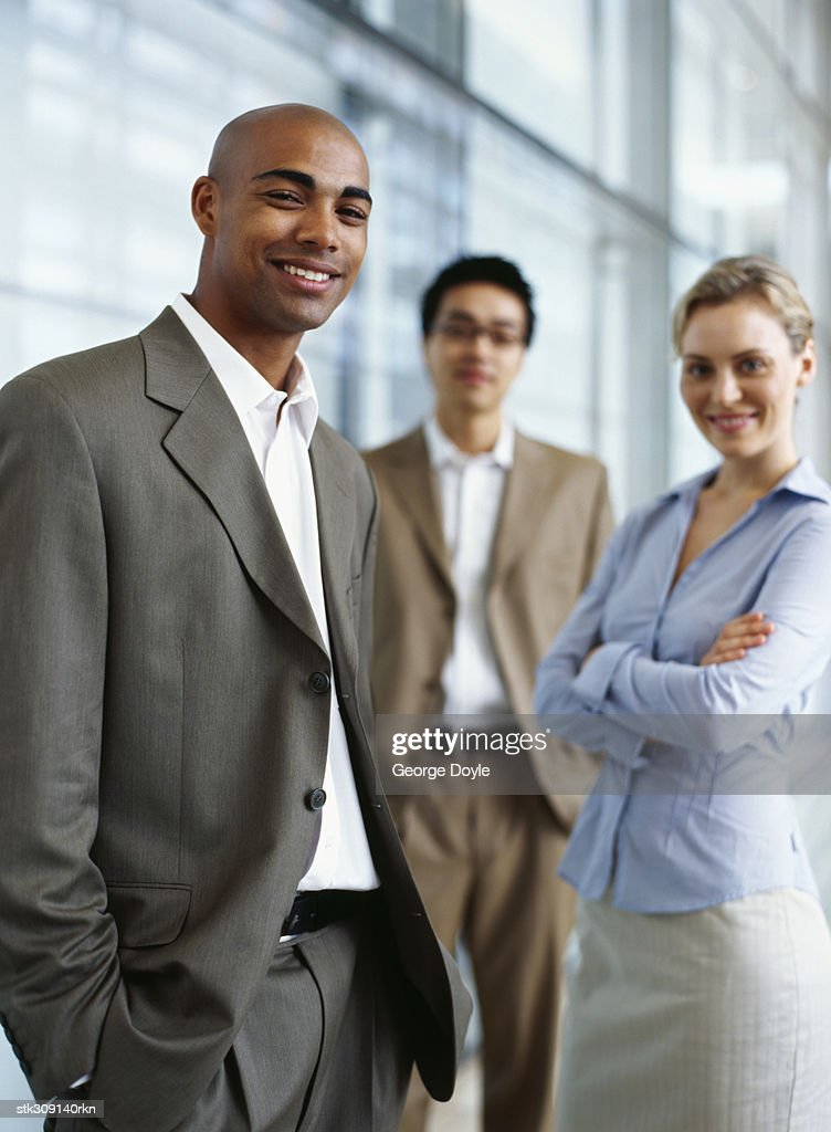 portrait of two businessmen and a businesswoman standing in an office : Stock Photo