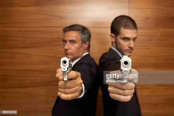 Portrait of two businessmen standing back to back and holding handguns