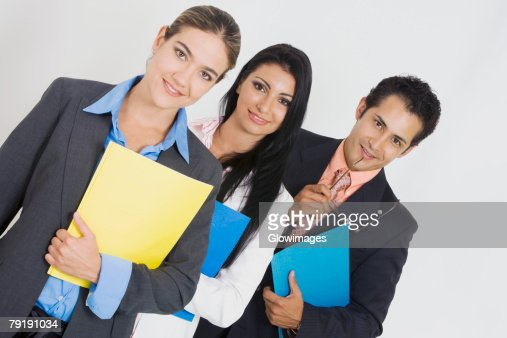 Portrait of two businesswomen and a businessman holding files and smiling : Foto de stock