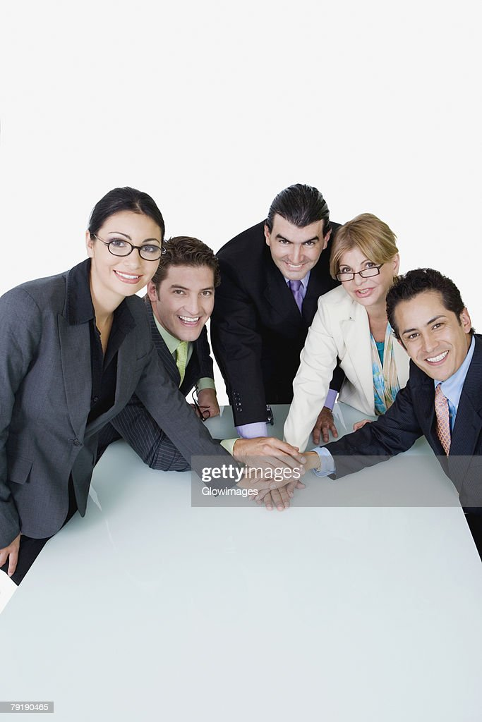 Portrait of two businesswomen and three businessmen placing their hands on each other : Foto de stock