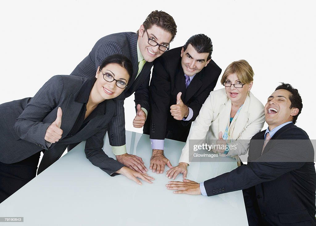 Portrait of two businesswomen and three businessmen placing their hands on the table : Foto de stock