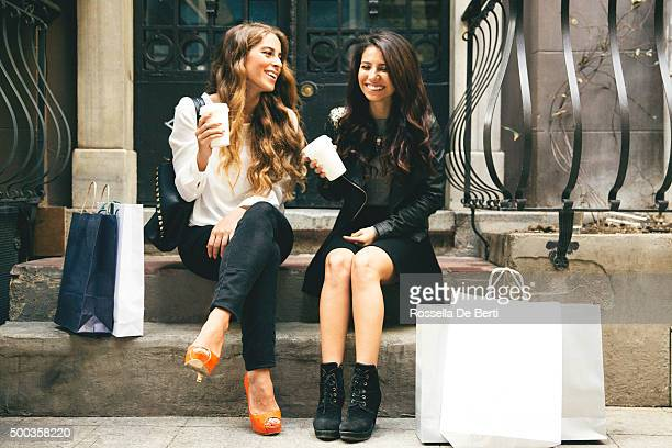Portrait Of Two Cheerful Women Having A Break After Shopping