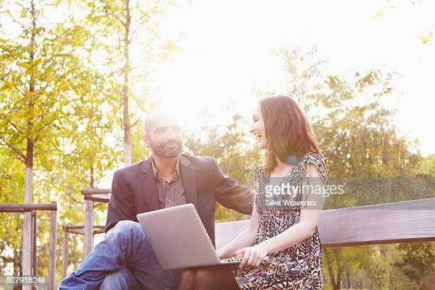 portrait of two colleagues working outside on a laptop sitting on a bench in a park, backlit.