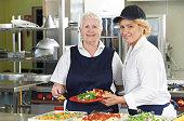 Portrait Of Two Dinner Ladies In School Cafeteria