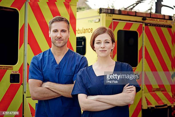 Portrait of two emergency medical technicians next to ambulance