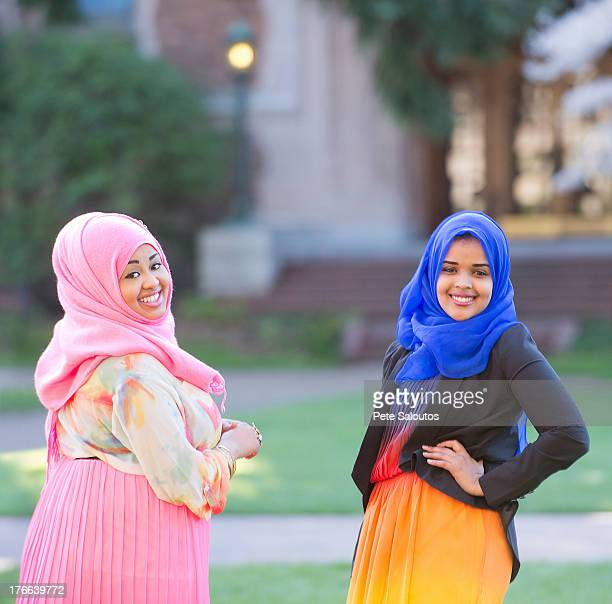 Portrait of two female friends in park wearing colorful headscarves