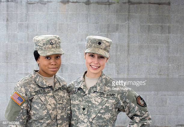 Portrait of Two Female Soldiers Against Brick Wall