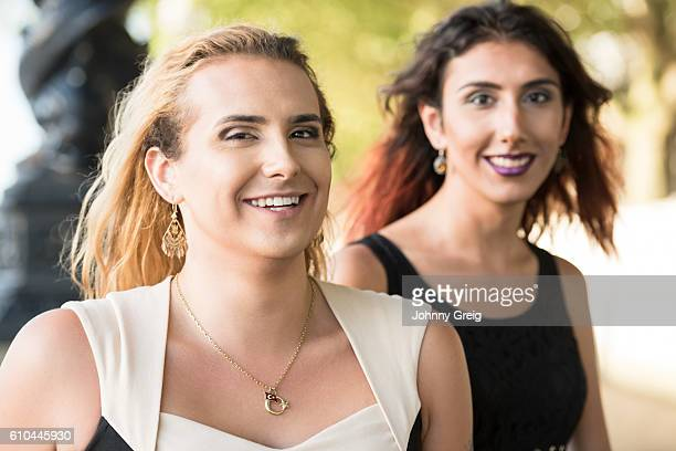 Portrait of two female transgender friends smiling towards camera