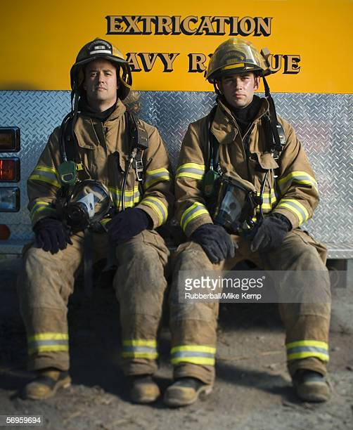 Portrait of two firefighters sitting