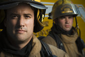Portrait of two firefighters wearing helmets
