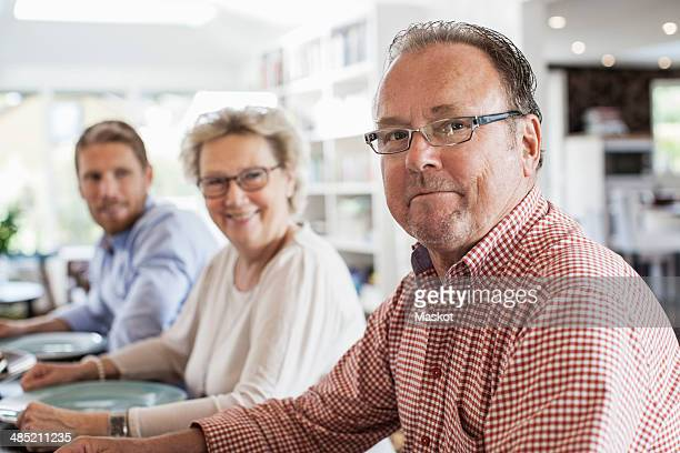 Portrait of two generation family sitting at dining table