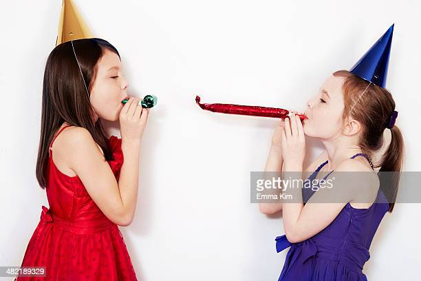 Portrait of two girls blowing party blowers